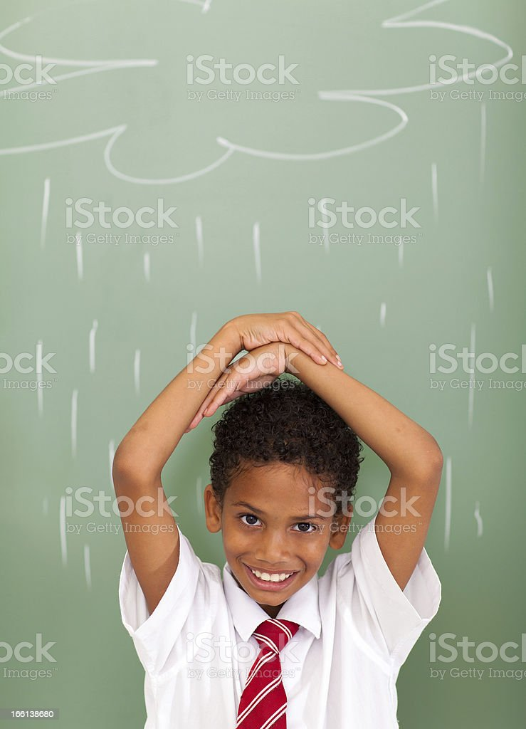 school boy in front of rain cloud drawn on chalkboard royalty-free stock photo