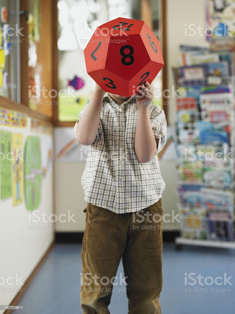 School Boy Playing with 12-Sided Die stock photo