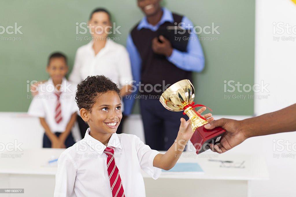 school boy receiving a trophy in classroom stock photo