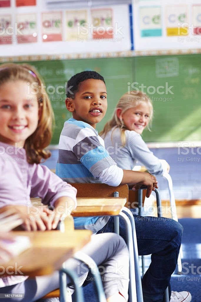 School boy sitting in classroom and looking behind royalty-free stock photo
