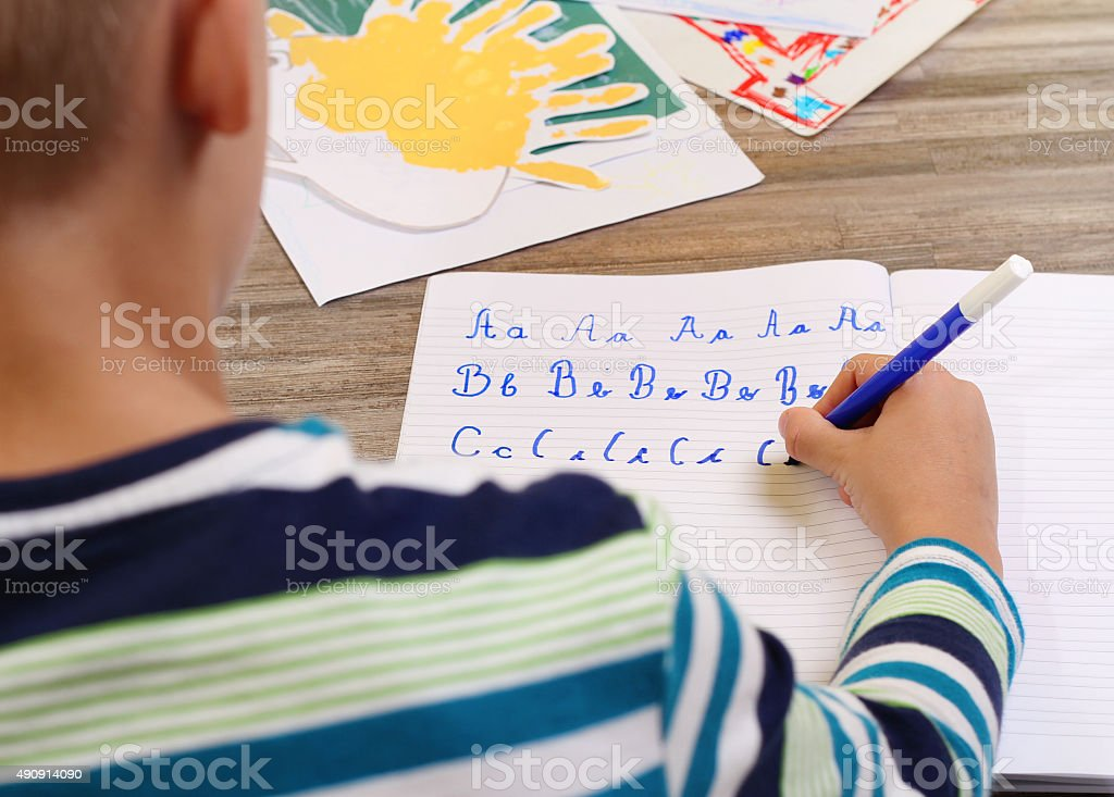 School Boy Writing on Paper  the alphabet with Pencil . stock photo
