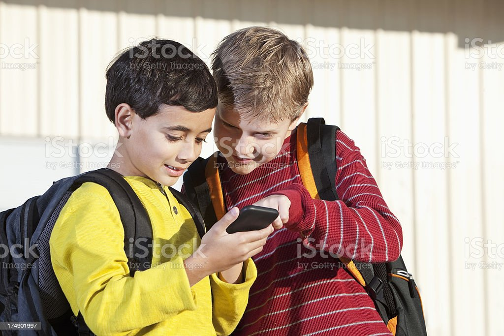 School boys using mobile device royalty-free stock photo