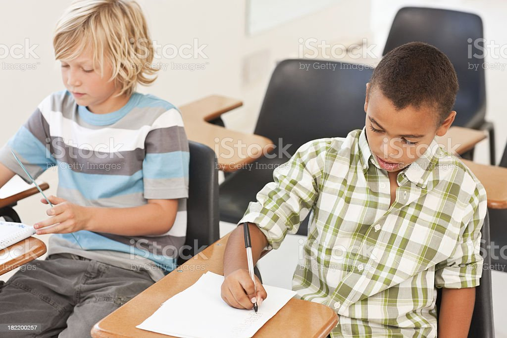 School boys writing notes in classroom royalty-free stock photo