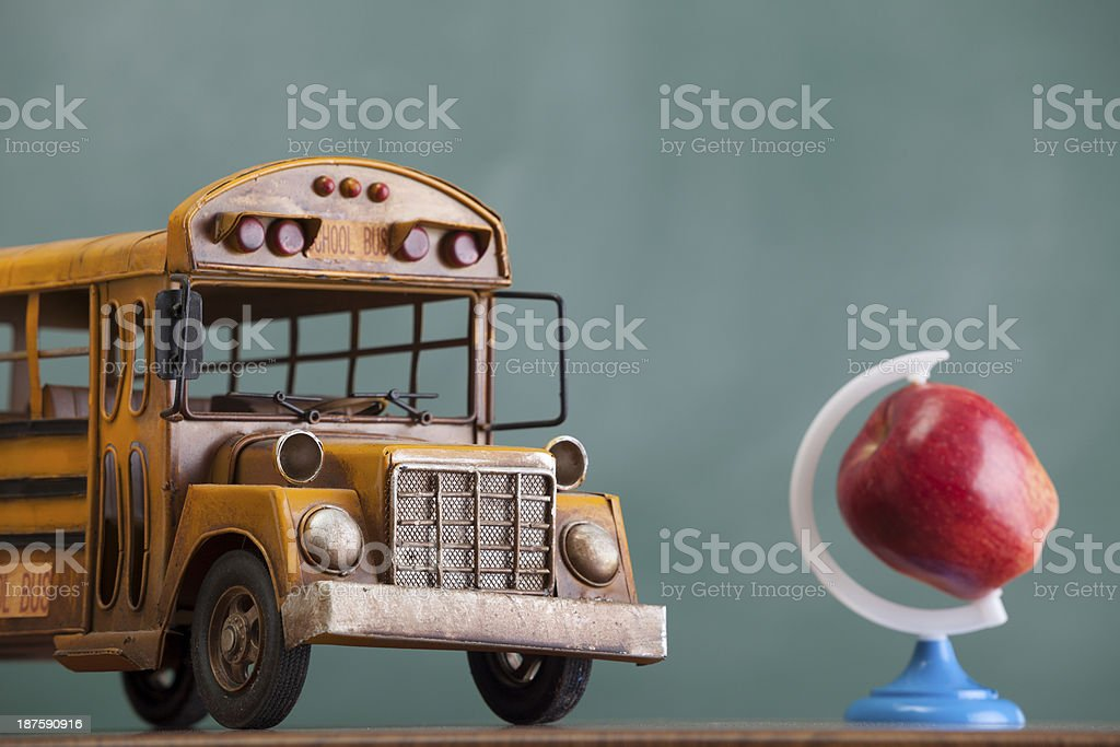 School bus and apple as globe on green chalkboard royalty-free stock photo
