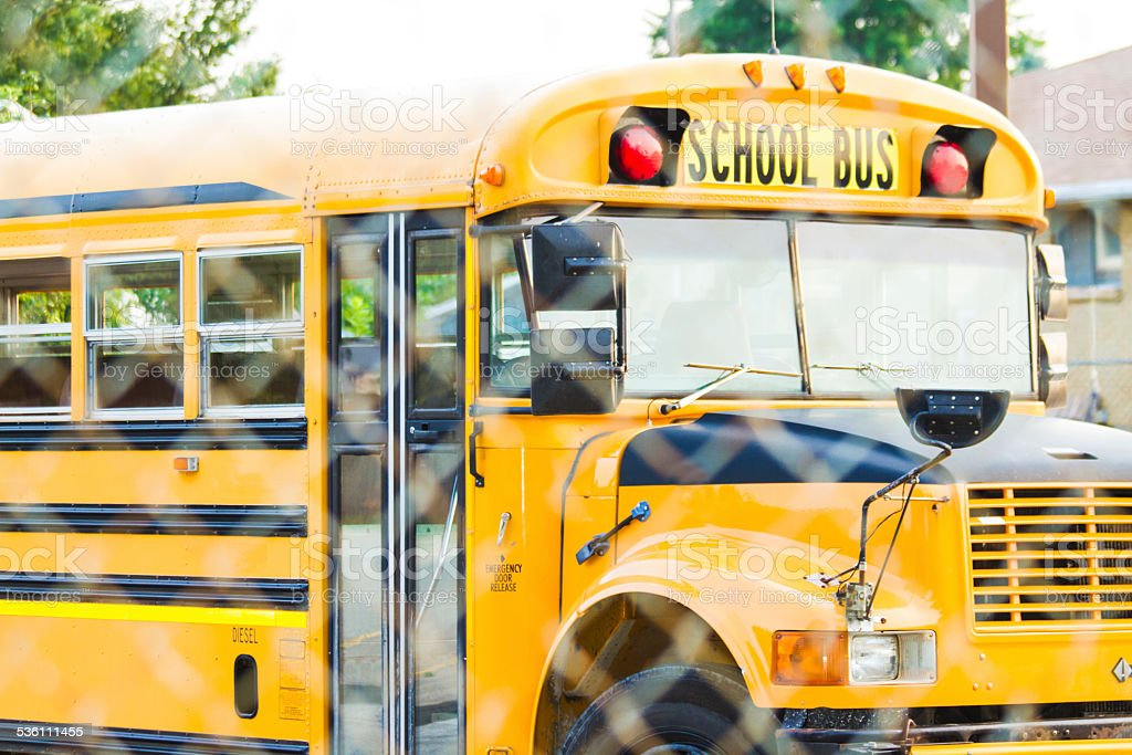School Bus Behind A Chain-link Fence stock photo