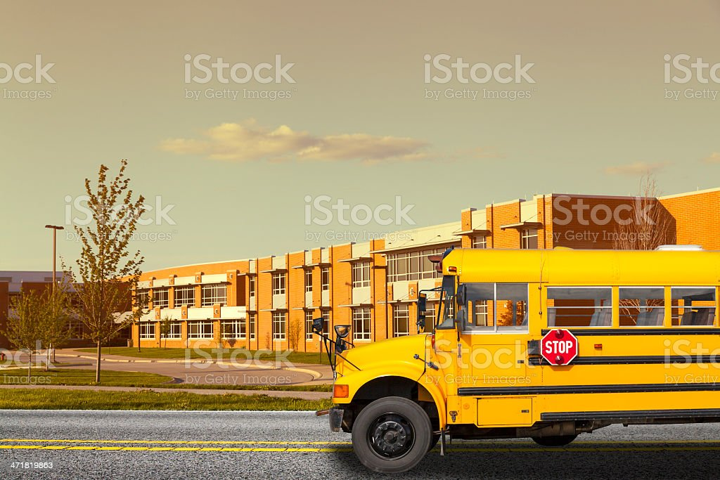 School bus in front of a school stock photo