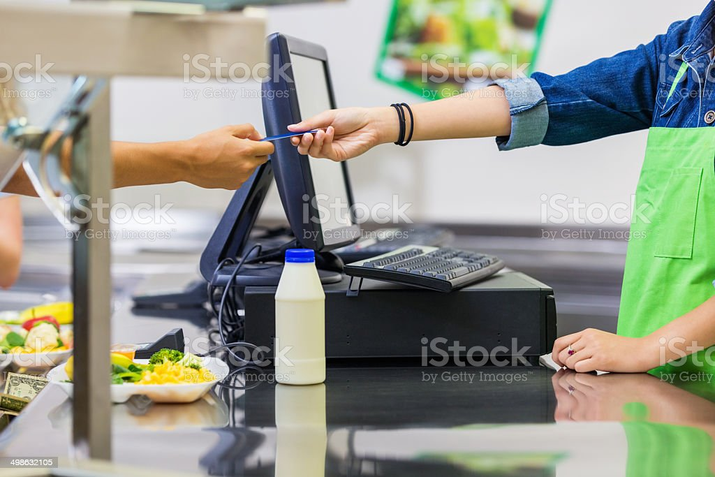 School cafeteria worker accepting credit card payment for meals stock photo