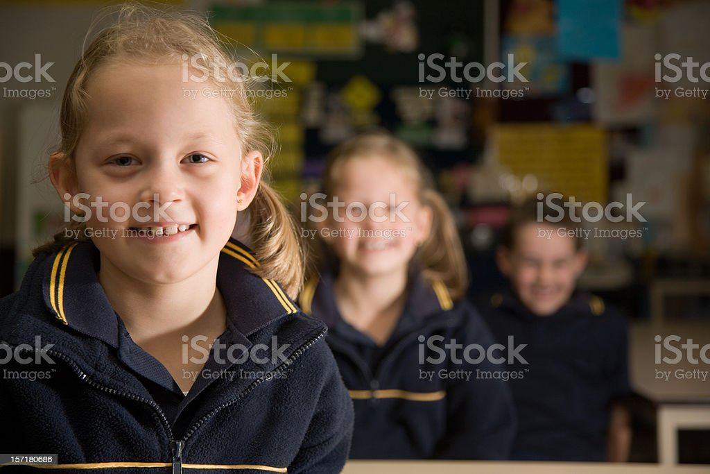 School children in uniform sitting in a row royalty-free stock photo