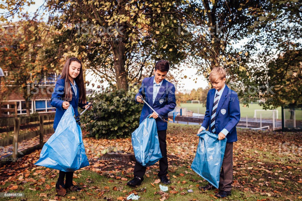 School Children Picking up Rubbish Around their School stock photo
