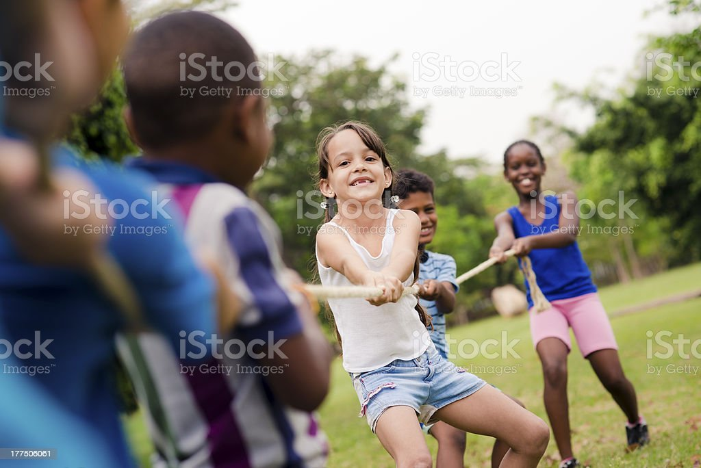 school children playing tug of war with rope in park stock photo
