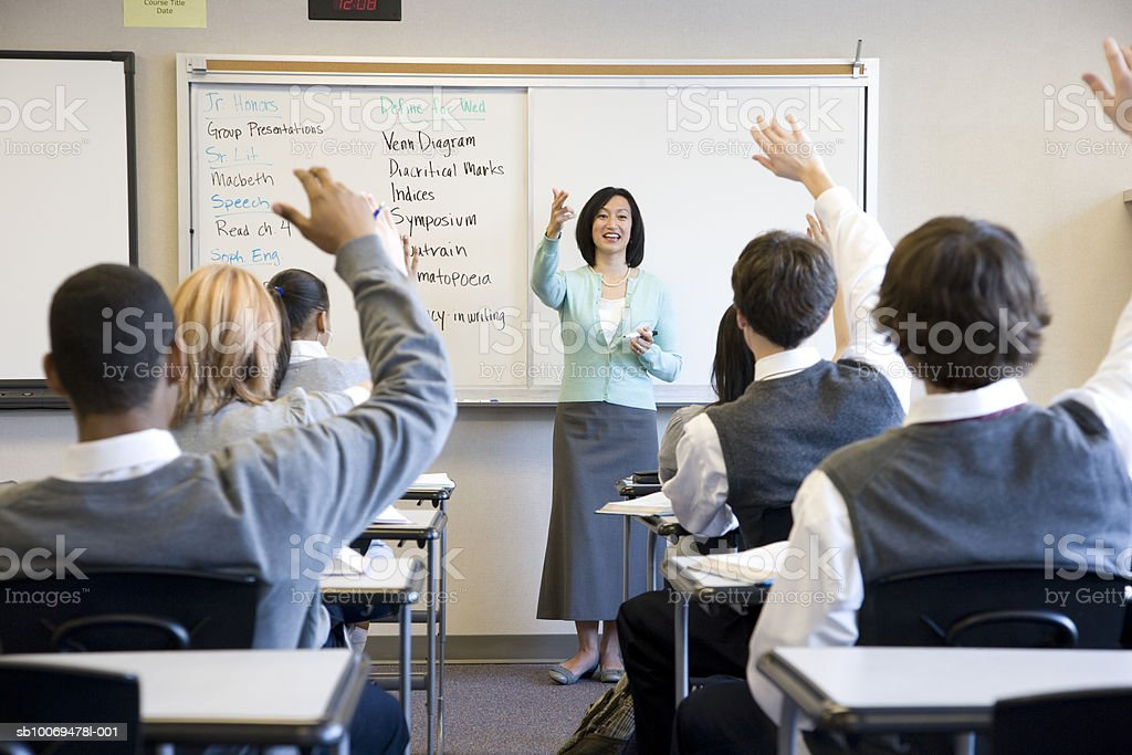 School children (14-18) raising hands in class stock photo