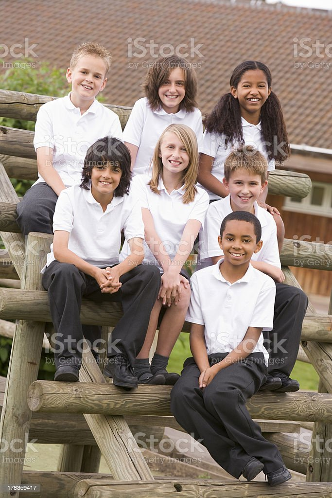 School children sitting on benches outside stock photo