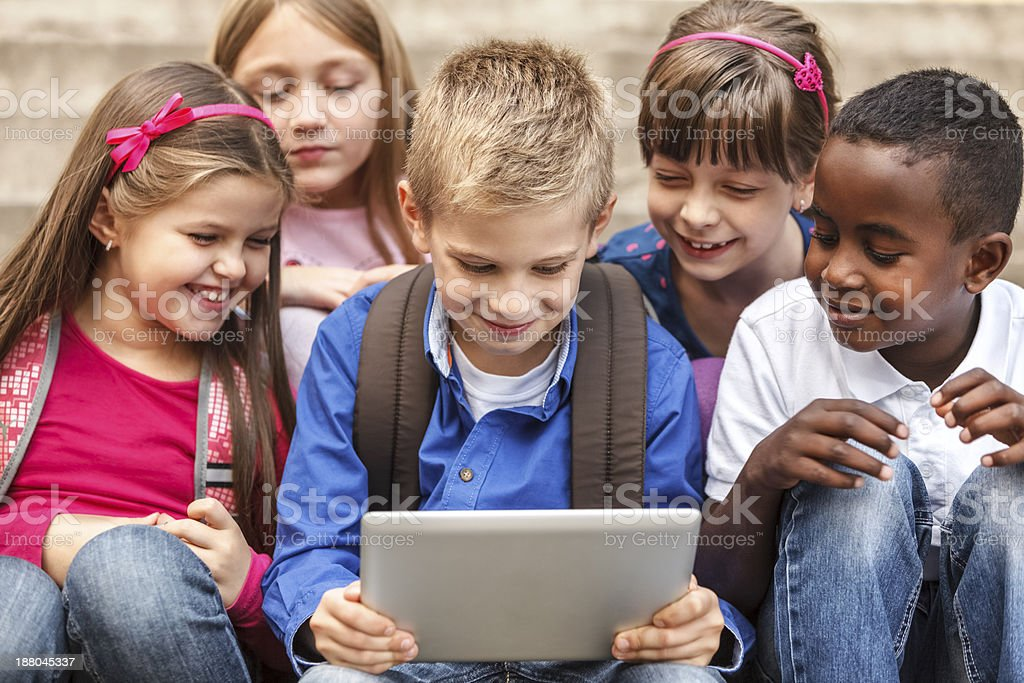 School children using digital tablet outside royalty-free stock photo