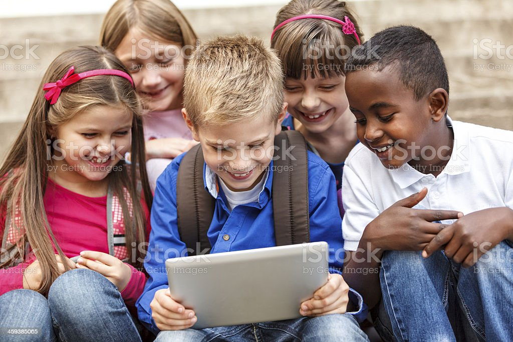 School children using digital tablet outside stock photo