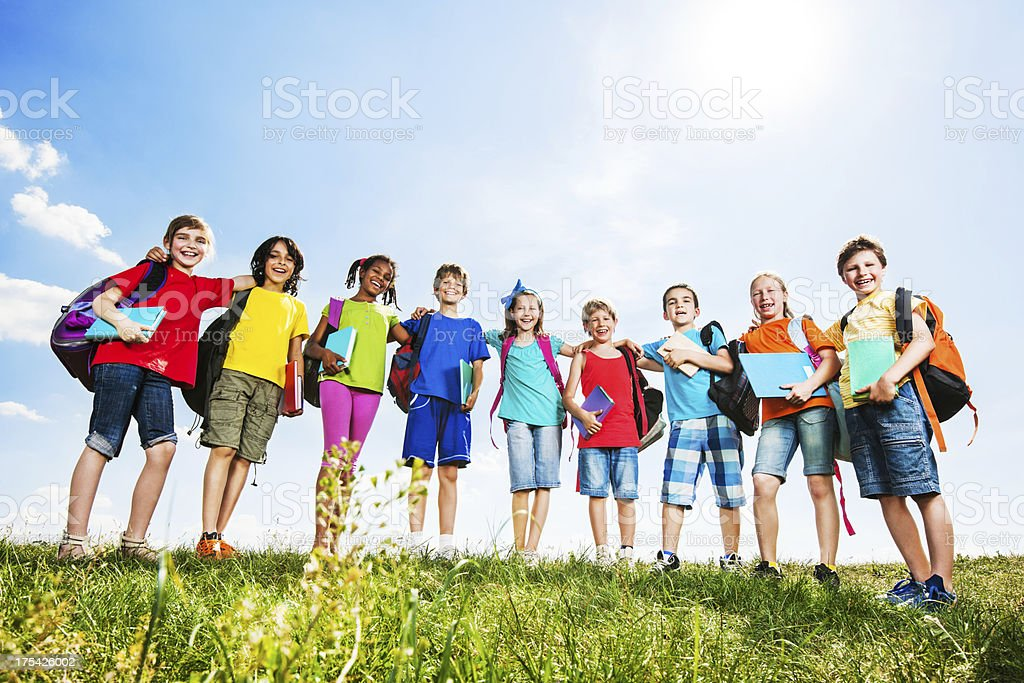 School children with backpacks and books against the sky. royalty-free stock photo