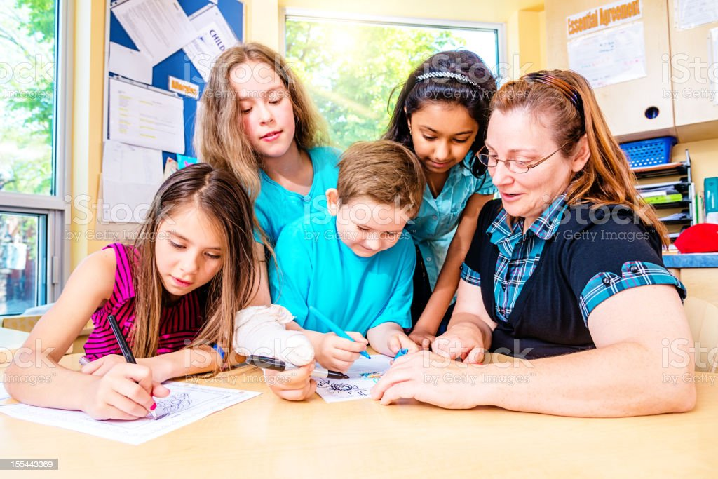 School Children Working Together with Teacher royalty-free stock photo