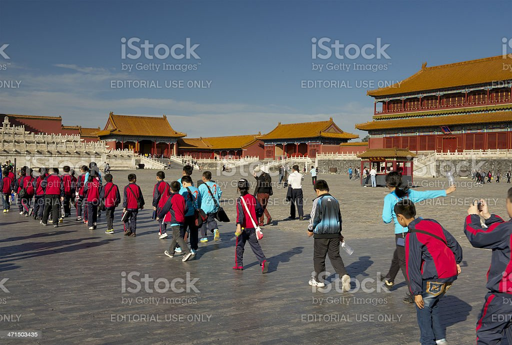 School class in red and blue uniforms visiting Forbidden City royalty-free stock photo