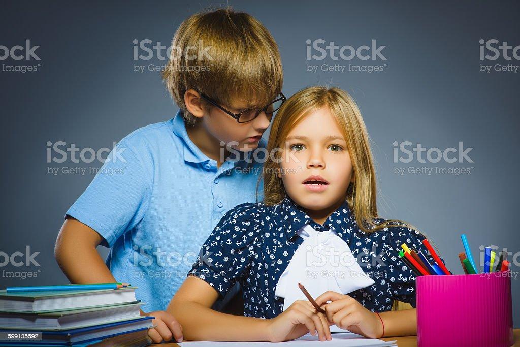 school Communication concept. boy whispering in ear of girl stock photo