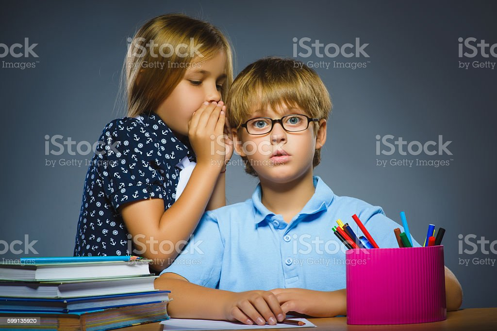 school Communication concept. girl whispering in ear of boy stock photo