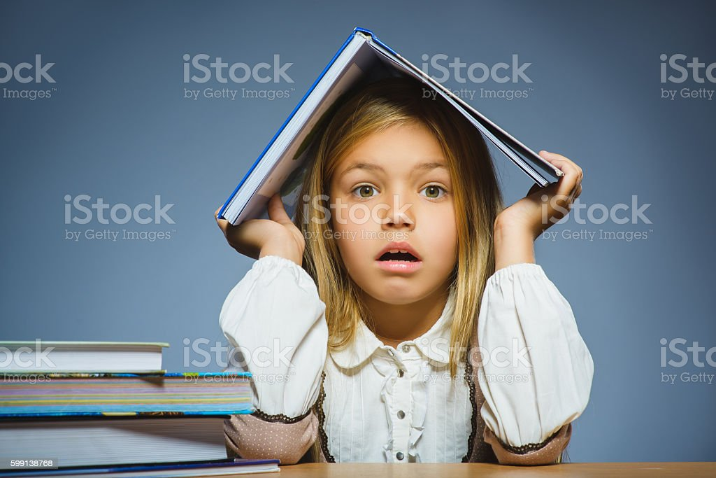 school concept. doubt girl sitting at desk and holding book stock photo