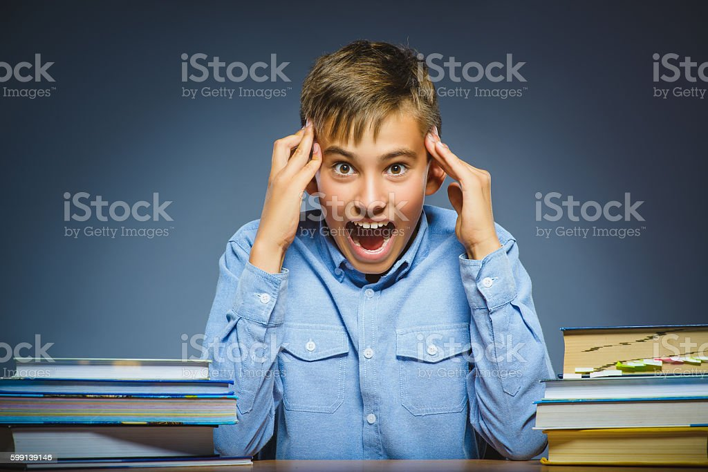 school concept. doubt or angry boy sitting at desk stock photo