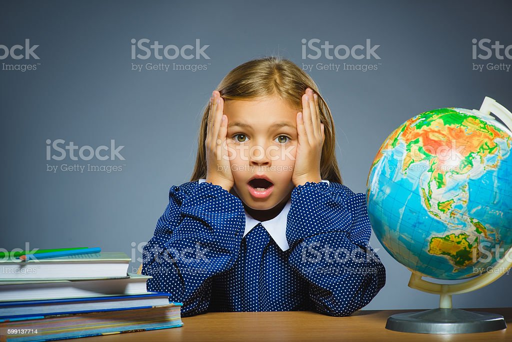 school concept. girl with astonished or doubt expression sitting at stock photo