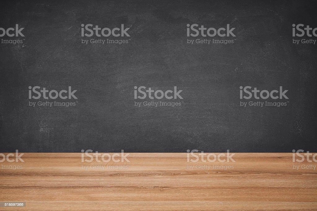 School Desk Against Black Chalkboard stock photo