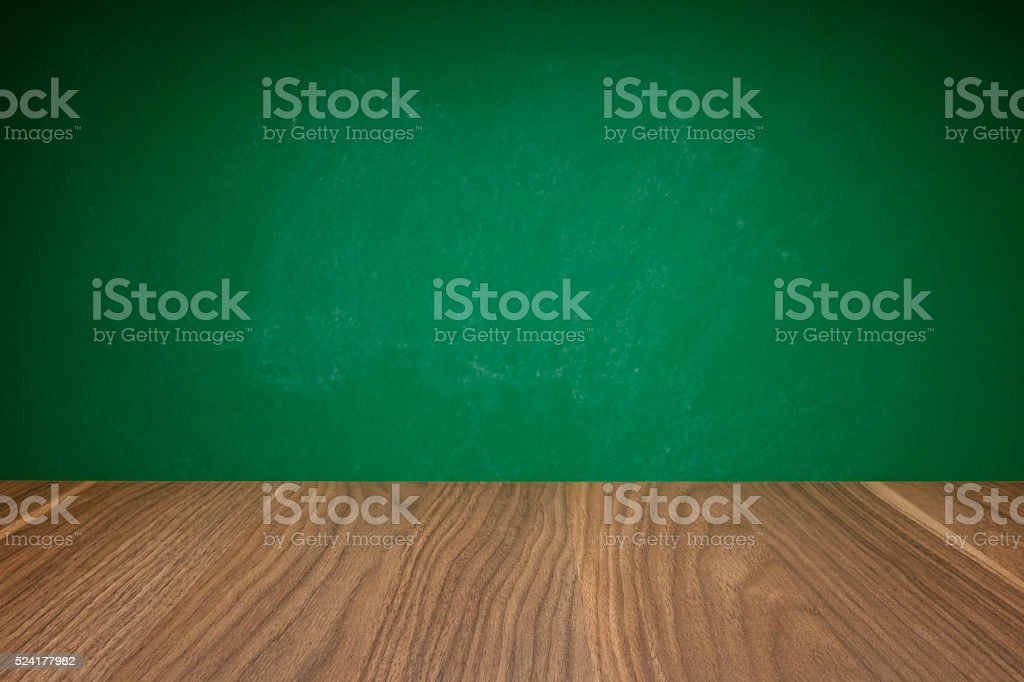 School desk against green chalkboard background stock photo