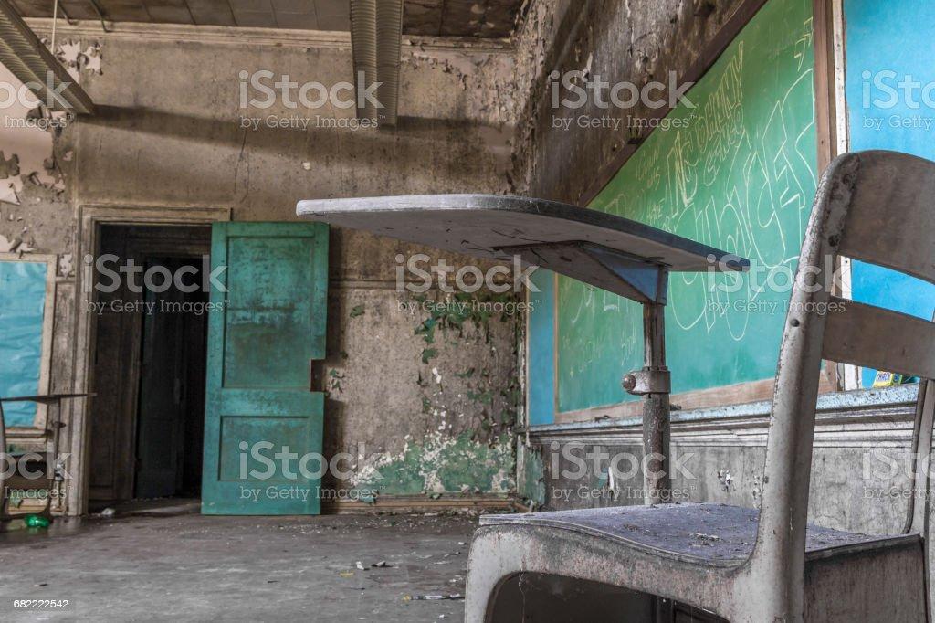 School desk in front of chalkboard in an abandoned school stock photo