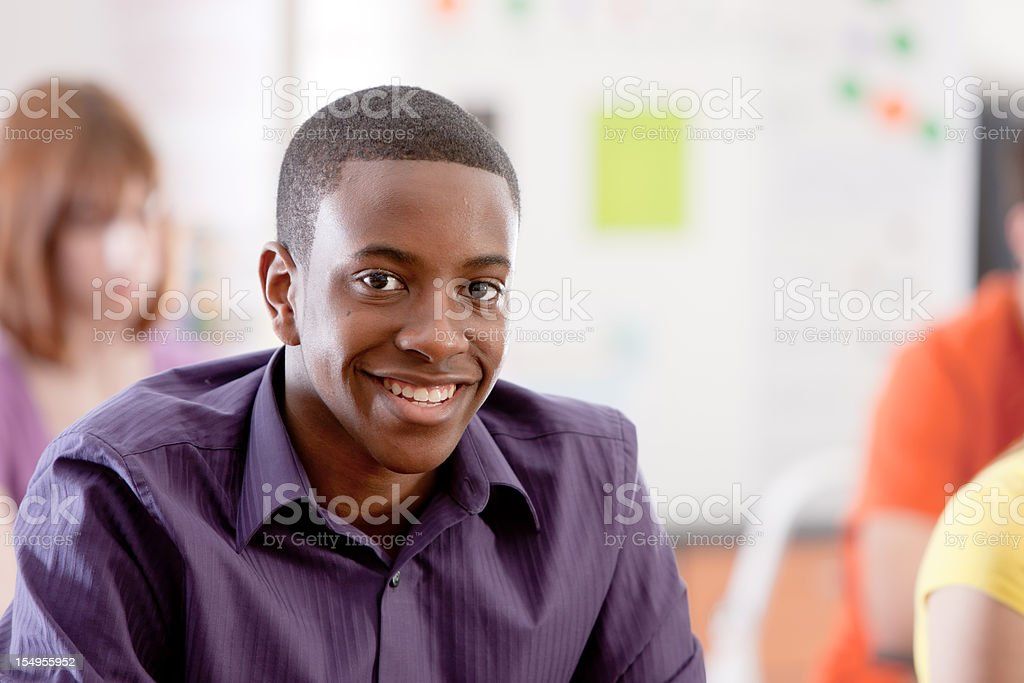 School Education: Smiling Teenage Boy in Classroom African American stock photo