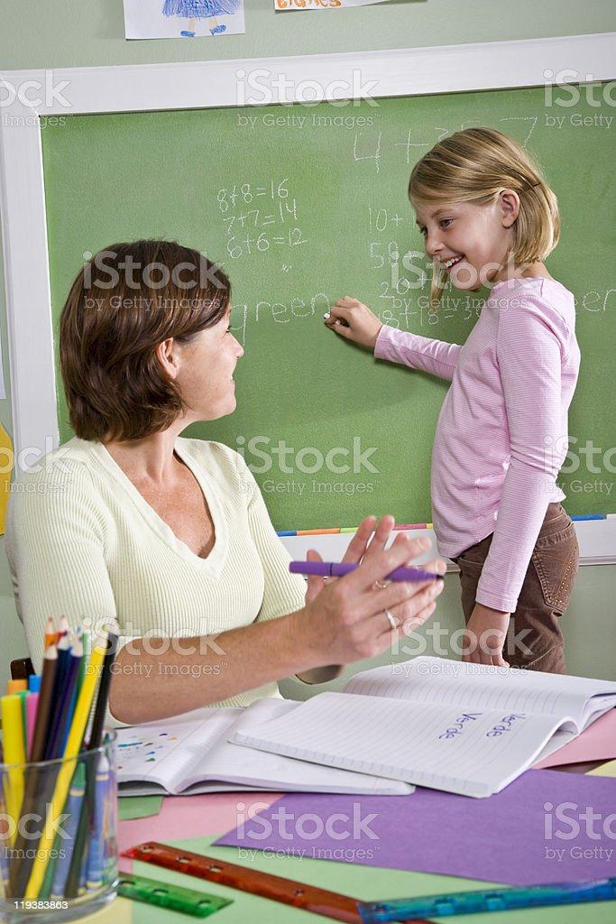 School girl and teacher by blackboard in classroom royalty-free stock photo