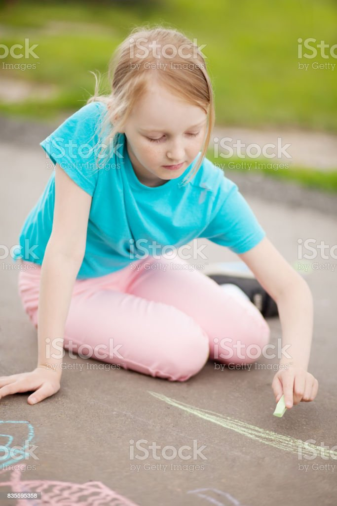 School girl drawing with piece of color chalk stock photo