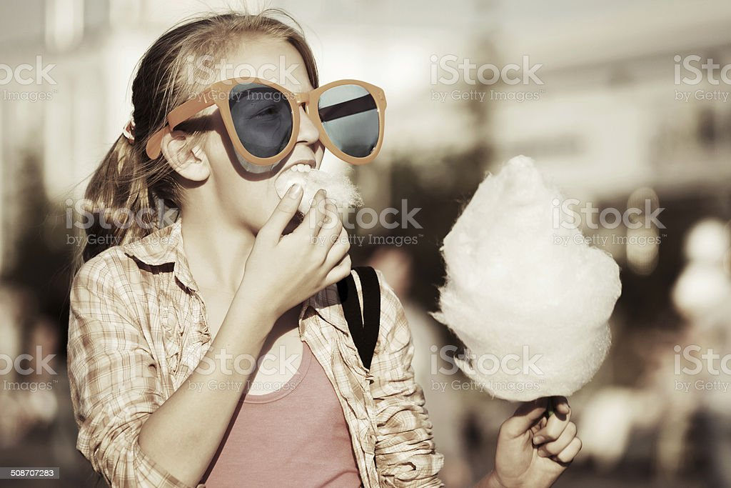 School girl eating cotton candy stock photo