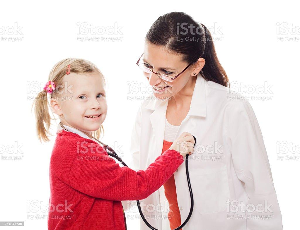 School Girl Examining Her Female Doctor, Studio Shot royalty-free stock photo
