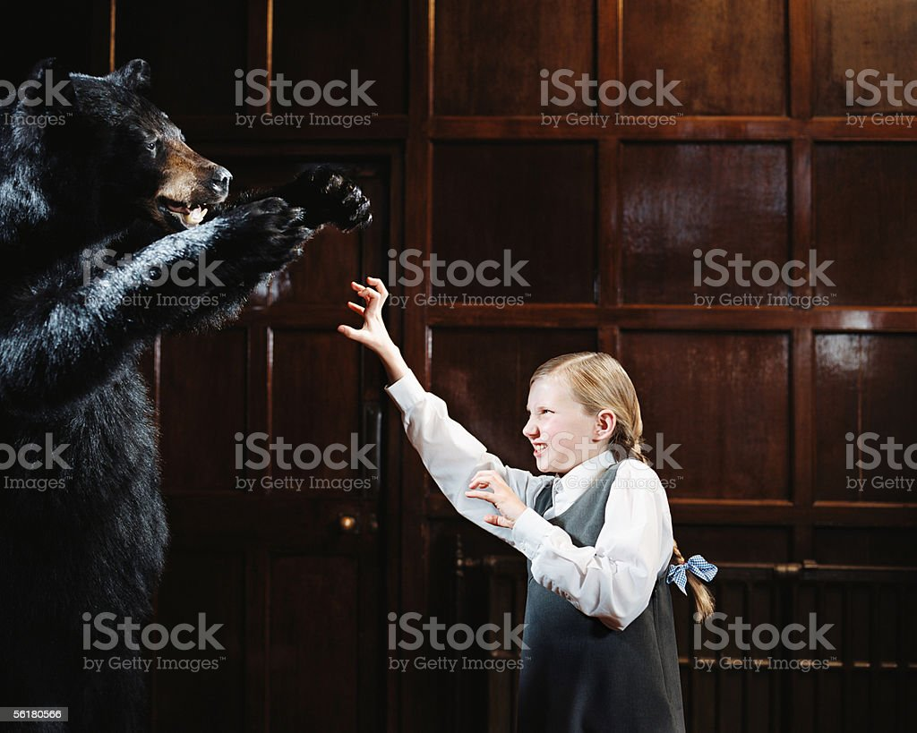 School girl growling at bear stock photo