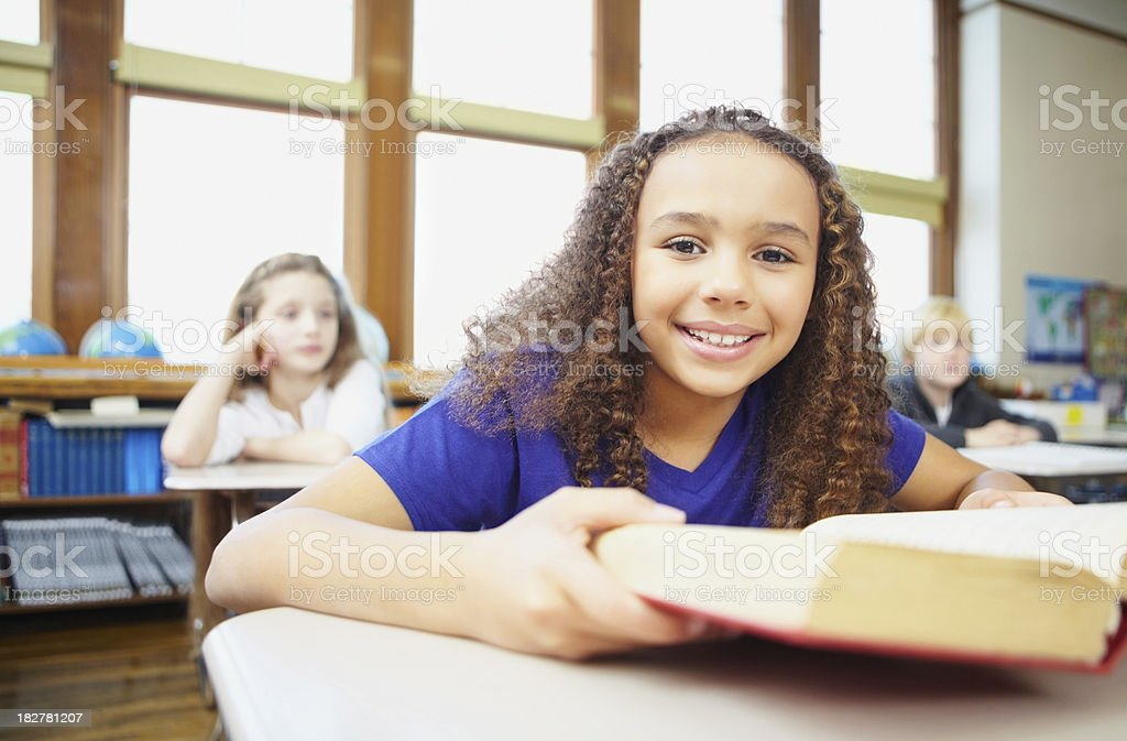School girl holding a book with students in background royalty-free stock photo