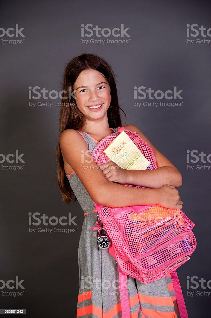 School girl holding her backpack stock photo