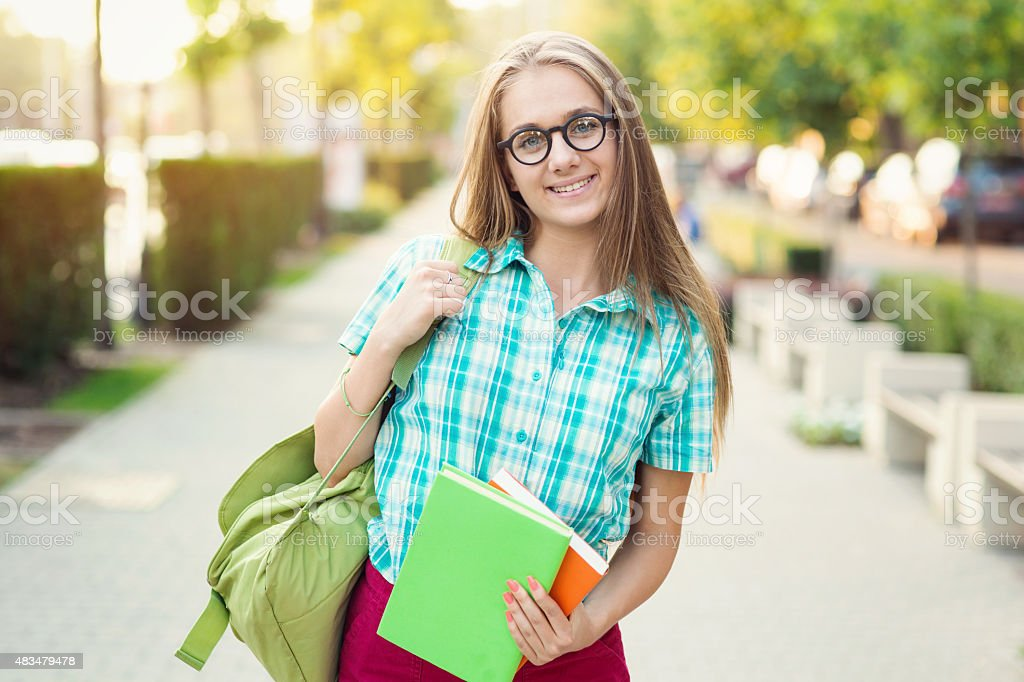 School girl holding textbooks on the street stock photo