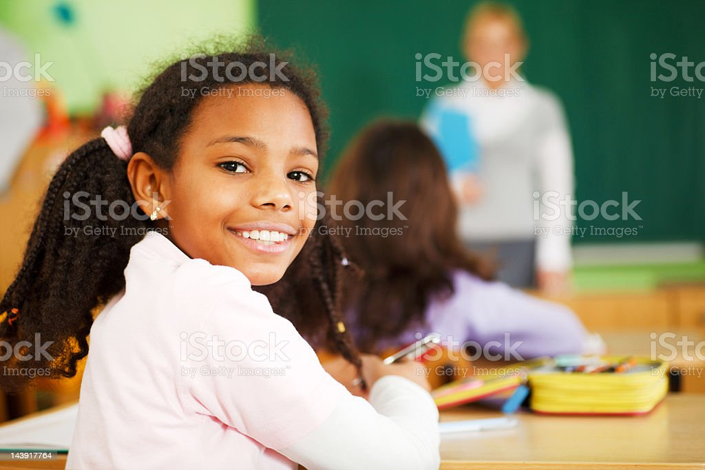 School girl looking behind and smiling. stock photo
