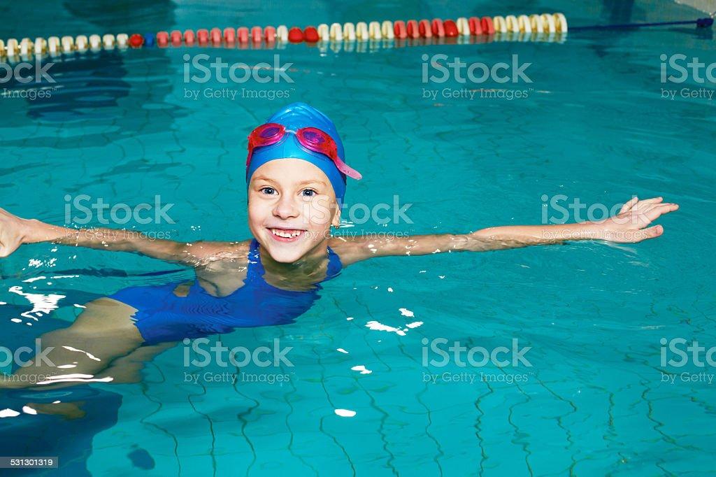 School girl swims in the sports pool stock photo