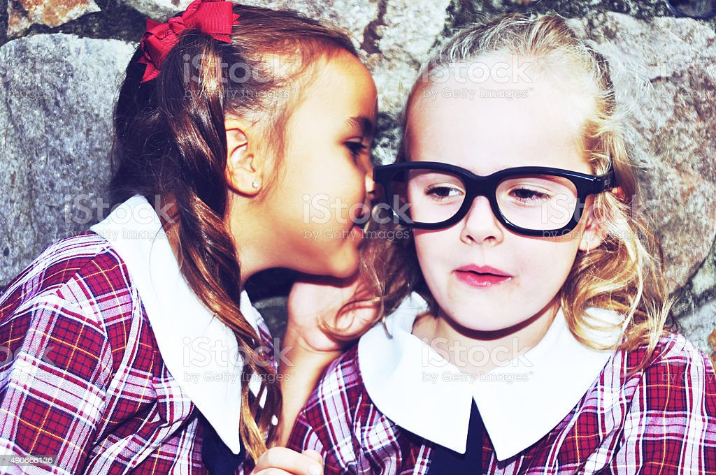 School girls telling secrets stock photo