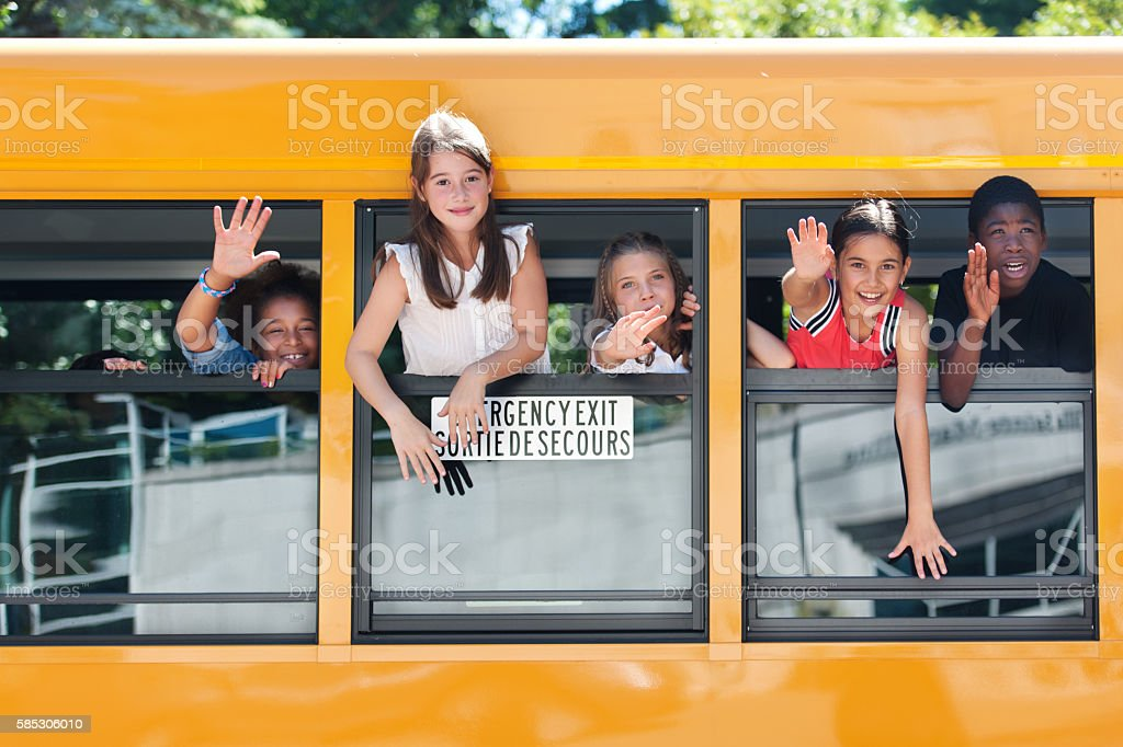 School kids hanging out bus windows stock photo
