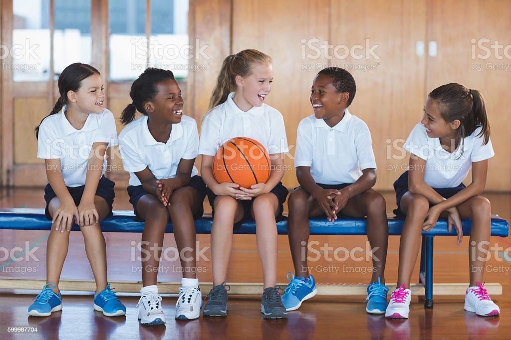 School kids having fun in basketball court stock photo