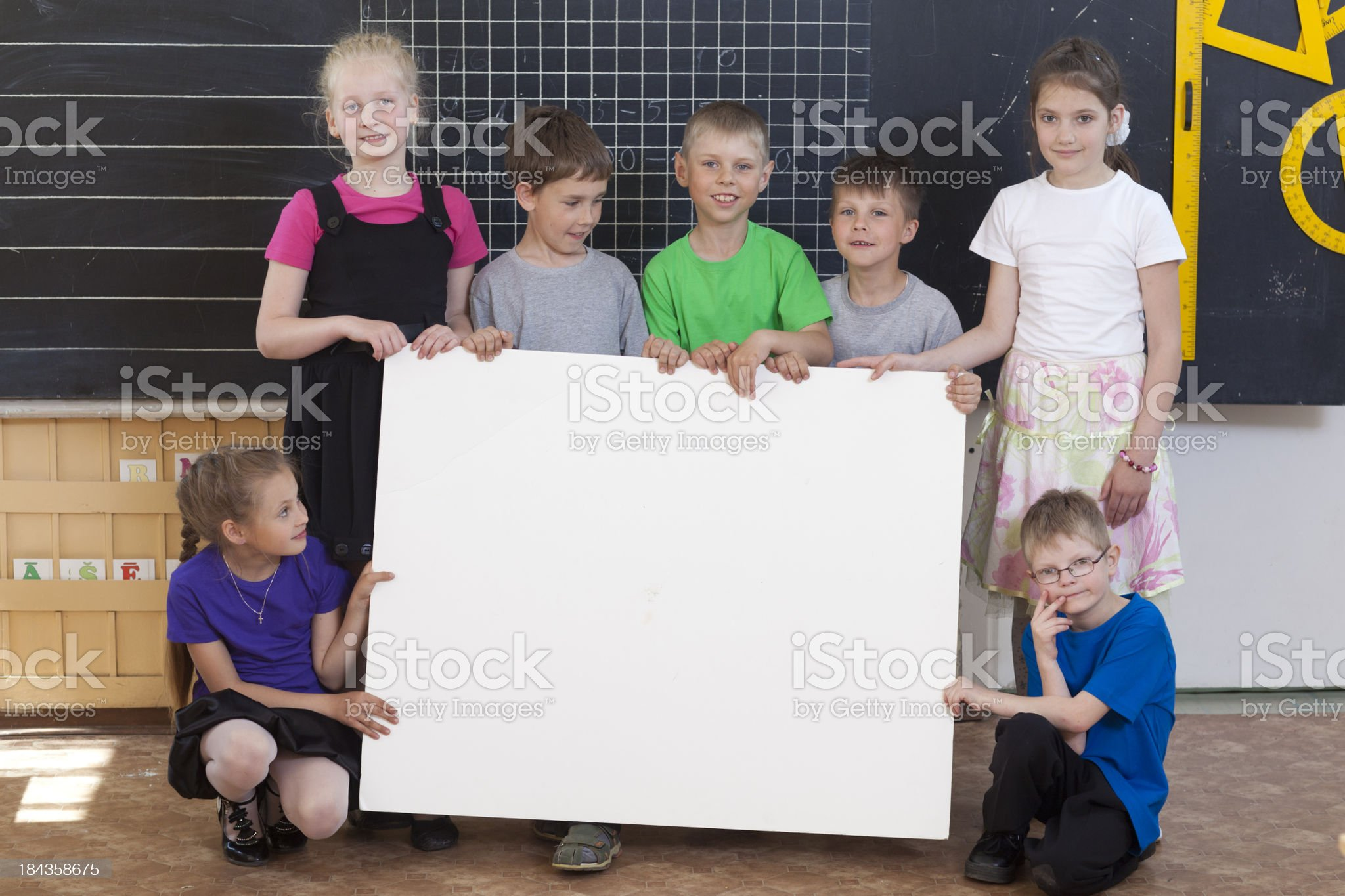 School kids holding blank informational sign royalty-free stock photo