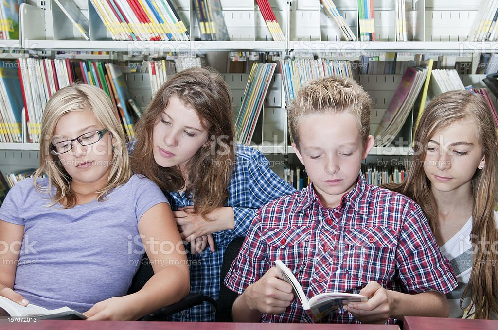School kids reading together in the library - I royalty-free stock photo