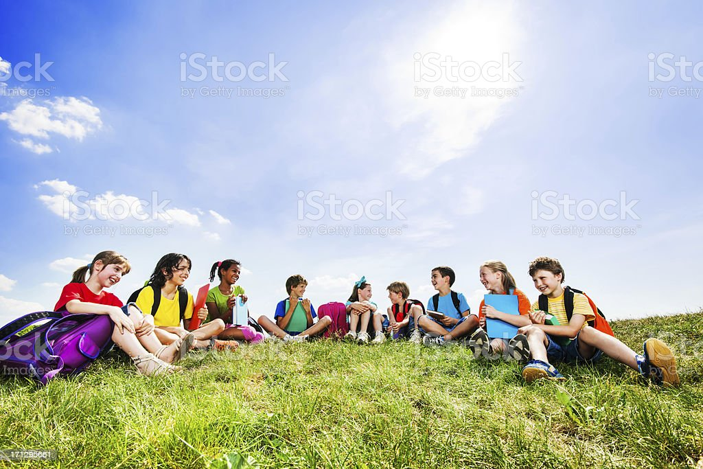 School kids sitting in the field. stock photo