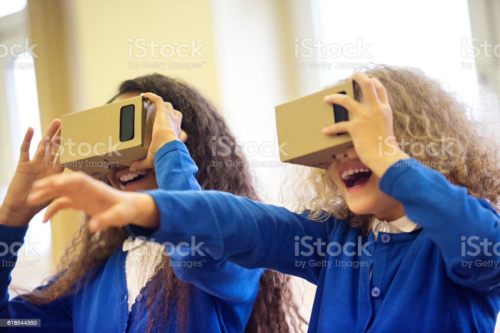 School kids using virtual reality goggles stock photo
