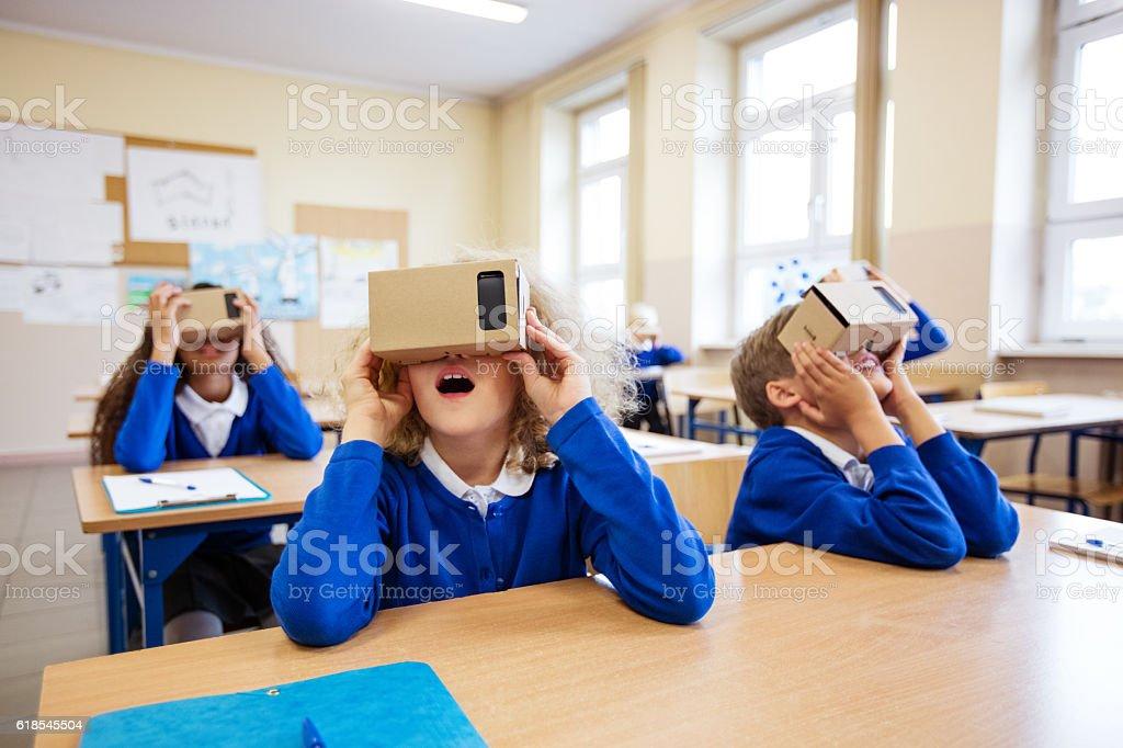 School kids using virtual reality goggles stock photo