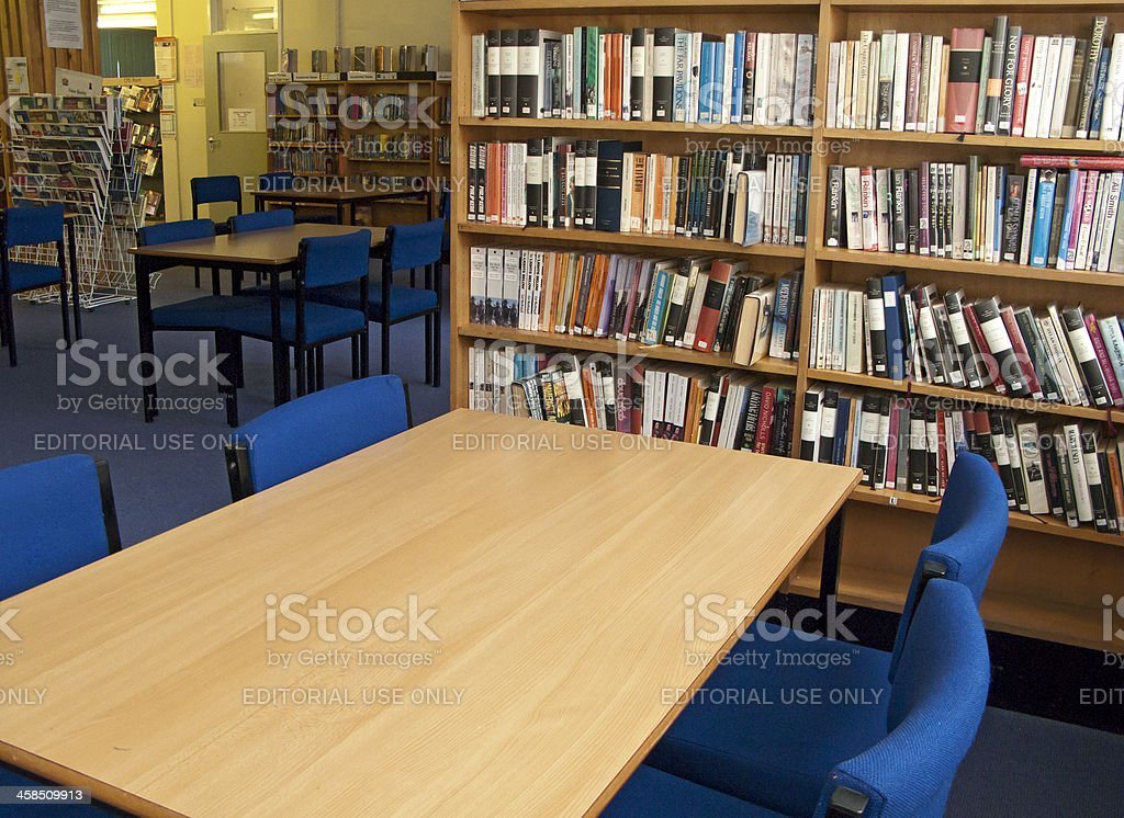 School library with tables, chairs and bookshelves royalty-free stock photo