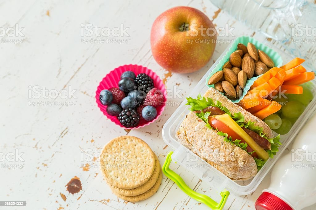 School lunch box with books and pencils in front of stock photo